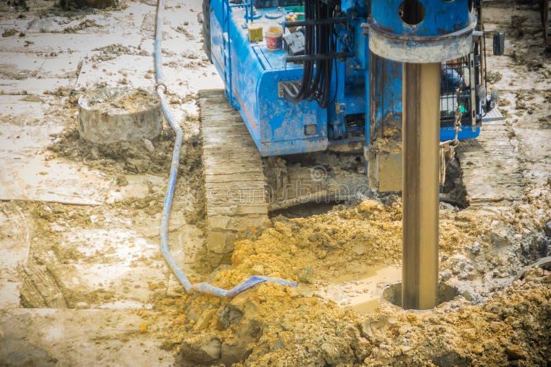 水力钻床在乏味堆工作的建造场所使孔不耐烦 乏味堆是钢筋混凝土elem 免版税库存照片