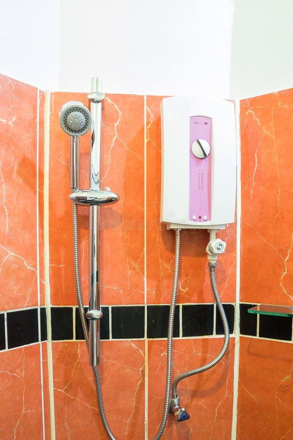 水加热器和阵雨在棕色卫生间里 库存图片
