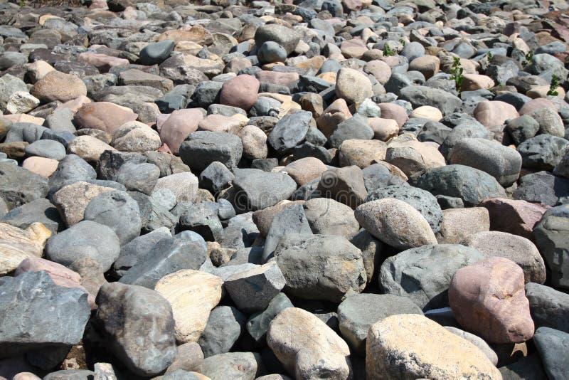 水向岩石样式扔石头 小卵石临近水 来回石头背景 背景蓝色云彩调遣草绿色本质天空空白小束 河床和岸 免版税库存图片