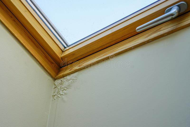 水和湿气损坏的天花板在屋顶窗口旁边 免版税库存照片
