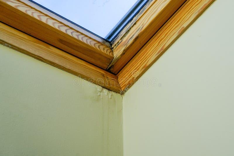 水和湿气损坏的天花板在屋顶窗口旁边 免版税库存图片