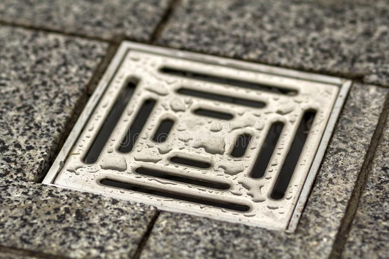 水在厨房、卫生间或者地下室陶瓷砖老葡萄酒地板的流失出气孔 几何抽象米黄背景 库存照片