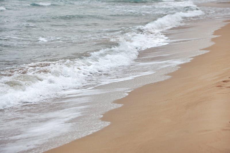 水在海滩的洗涤物沙子在阴暗天 在小白色波浪形成的细节 抽象背景海运 库存图片