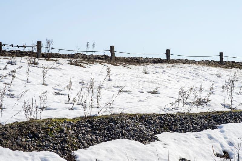 水坝的设备以灰色石渣的一个被加强的堤防的形式与一条路的在上面 免版税库存照片
