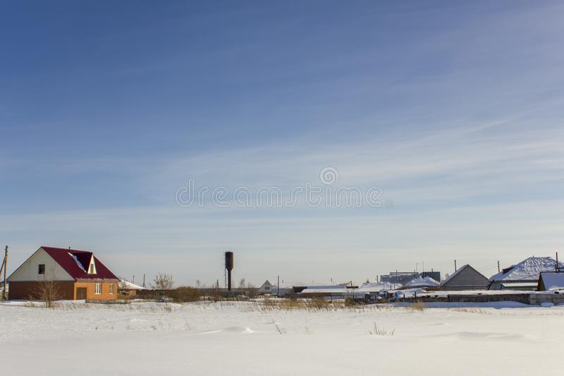 水塔和现代村庄房子在一天空蔚蓝下与白色云彩在冬天 免版税库存图片