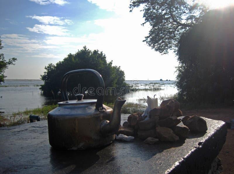 水壶、岩石和蜡烛在一块平板早晨太阳 库存图片
