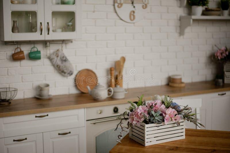 水壶和平底深锅在厨房用桌上 反对白色厨房背景的厨房器具 免版税库存照片