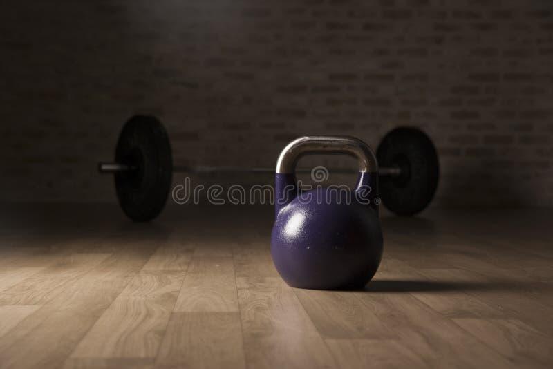 水壶响铃和举重酒吧在一间木地板健身房 图库摄影