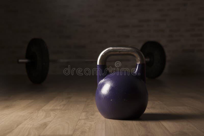 水壶响铃和举重酒吧在一间木地板健身房 库存图片