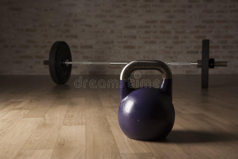 水壶响铃和举重酒吧在一间木地板健身房 免版税图库摄影