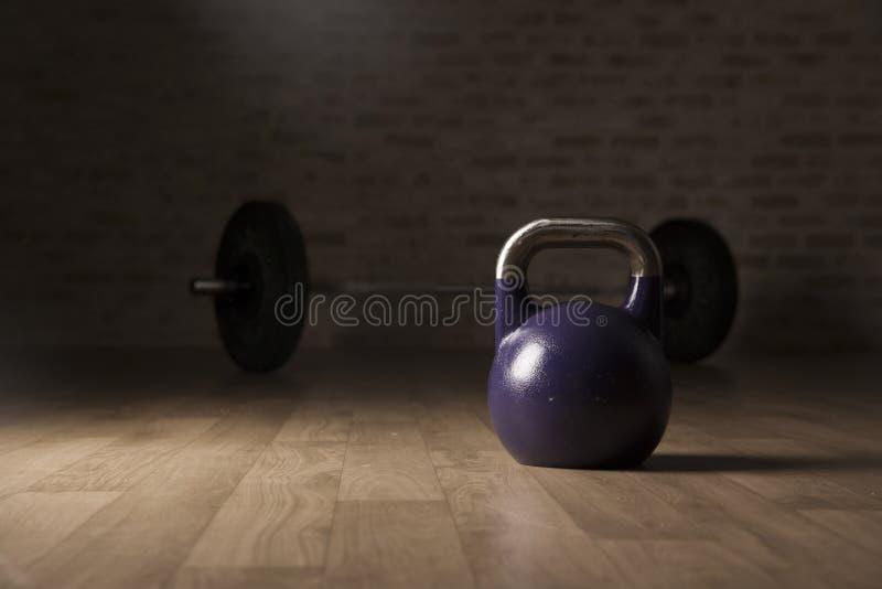 水壶响铃和举重酒吧在一间木地板健身房 库存照片