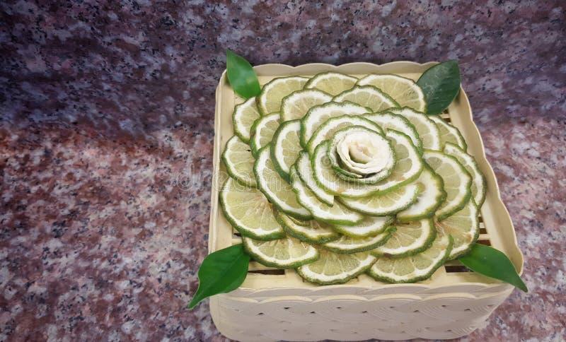 水多的切片Makrut或非洲黑人石灰用在木桌上的绿色香柠檬 免版税库存照片