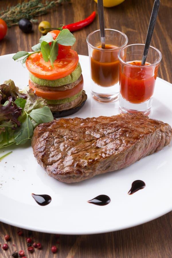 水多的新近地烤牛排供食与辣酱和菜 免版税库存照片