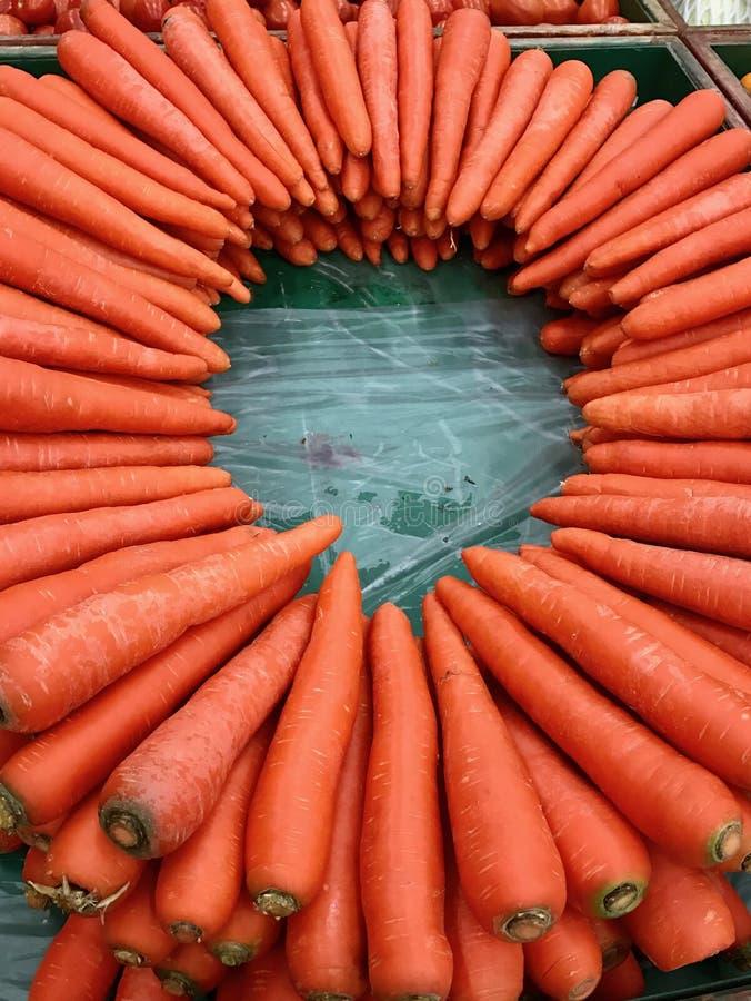 水多的橙色红萝卜在一张木桌上的一个圈子安排了 库存照片
