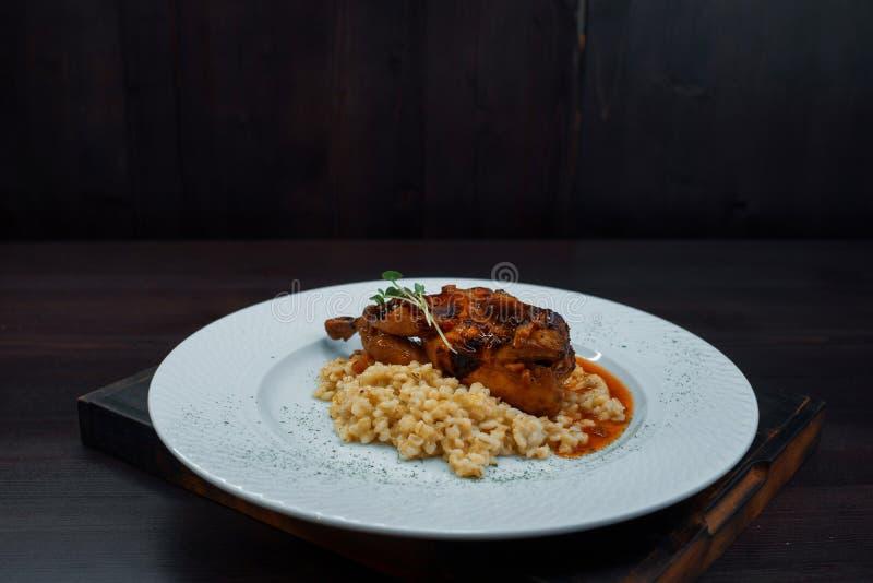 水多的烤鸭肉用粥用在一张木葡萄酒桌上的烤肉汁在餐馆 热的好吃 免版税库存照片