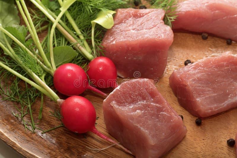 水多的肉片在有调味料、草本和菜的一块木板材服务 免版税库存图片