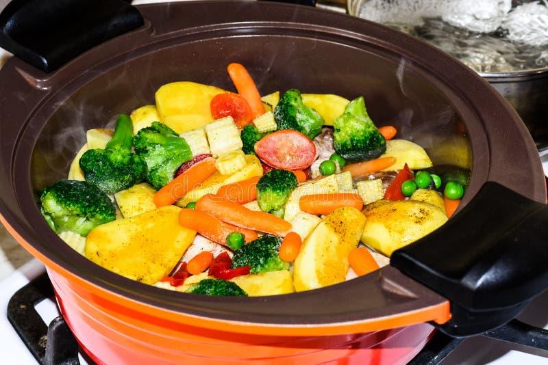 水多的菜炖煮的食物,在橙色陶瓷罐的火炉 素食主义 库存照片
