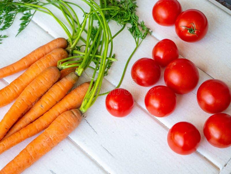 水多的蕃茄和红萝卜、健康吃的概念和减肥 免版税库存图片