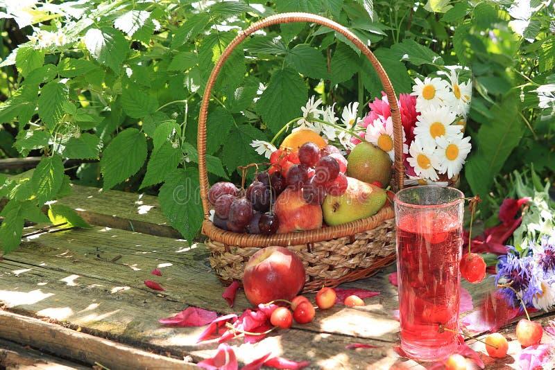 水多的黑葡萄和苹果、梨和桃子在一个篮子在庭院里在一张老木桌上, 免版税库存照片