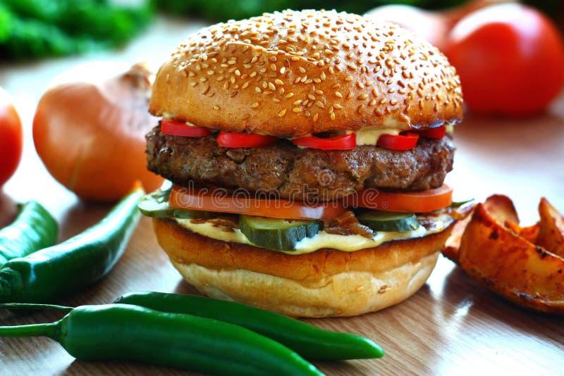 水多,辣汉堡用牛肉和红辣椒,在与菜的一张桌上 免版税库存照片