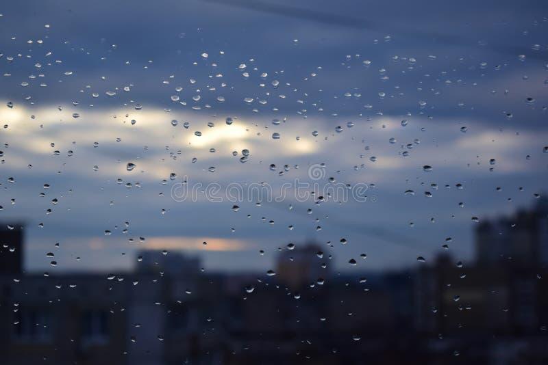 水小滴在一块玻璃的在城市和天空背景  库存图片