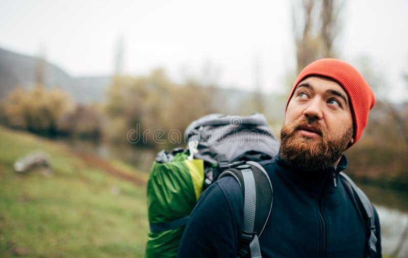 水平的室外画象的关闭徒步旅行者年轻男性远足在与旅行背包的山 免版税库存图片