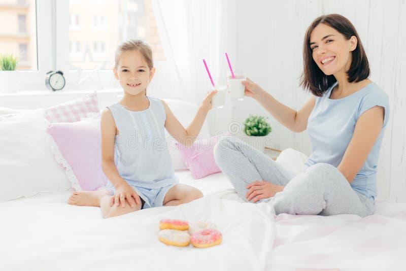 水平的射击俏丽女性和她的女儿使与鸡尾酒的玻璃叮当响在床上,食用早餐在卧室,吃可口窦 免版税库存照片