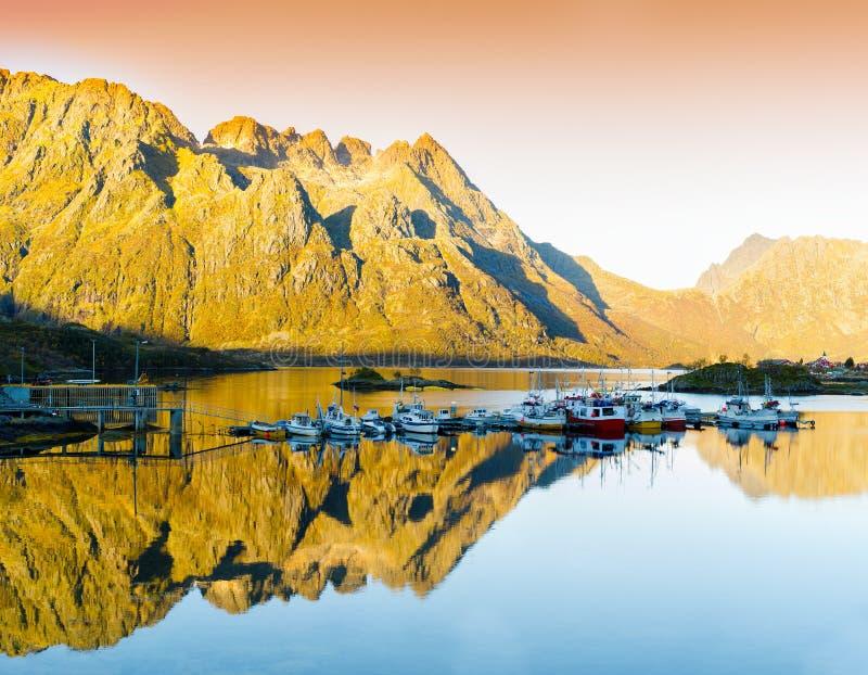 水平的生动的橙色日落在挪威海湾反射土地 图库摄影