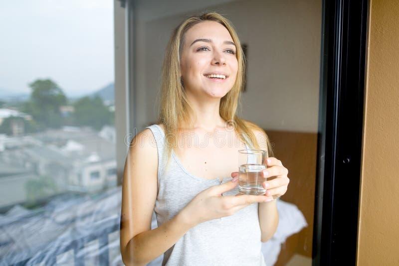 水年轻白种人女性水杯在早晨在旅馆 免版税库存图片