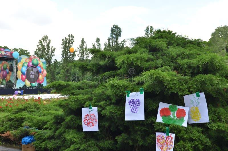 水彩垂悬在树的儿童的绘画在公园 免版税库存图片