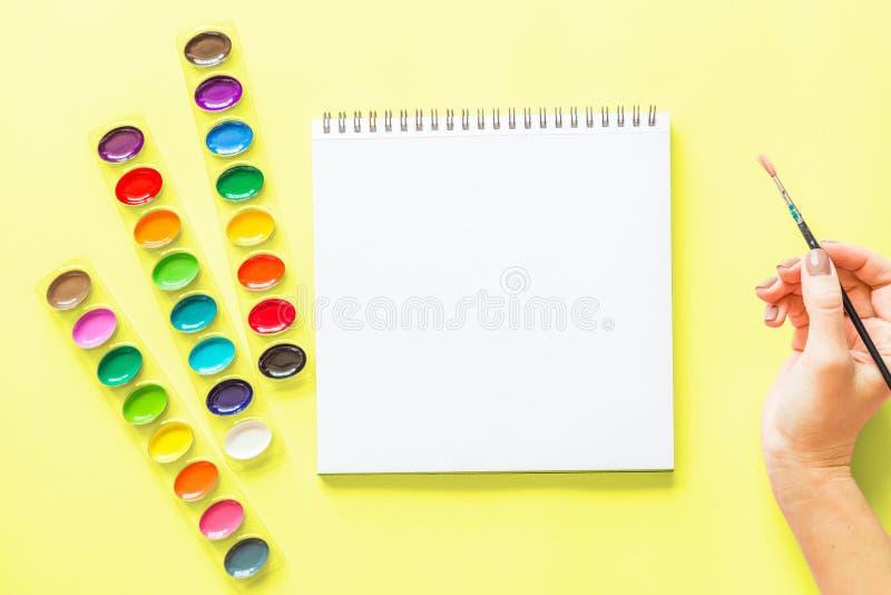 水彩调色板创造性的平的位置,笔记本,拿着画笔的女性手 黄色背景的艺术家工作场所 免版税库存图片