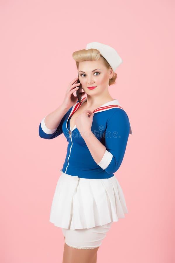 水手打扮了有智能手机的女性在桃红色背景 有卷毛的白肤金发的女孩和画报化妆谈话在多孔 免版税库存图片