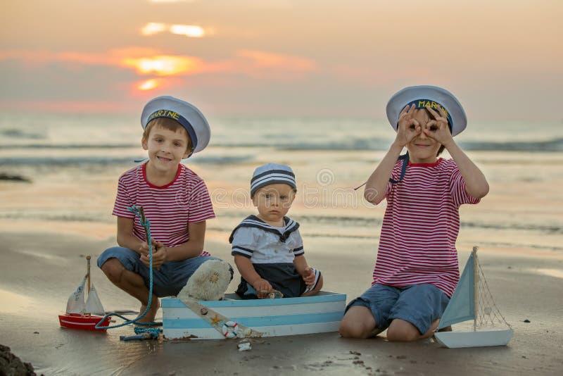 水手男婴,逗人喜爱的孩子,使用在与木bo的海滩 免版税库存图片