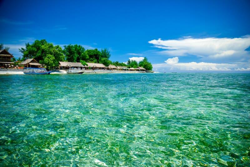 水晶水和海滩与平房在背景苏门答腊,印度尼西亚中 库存照片