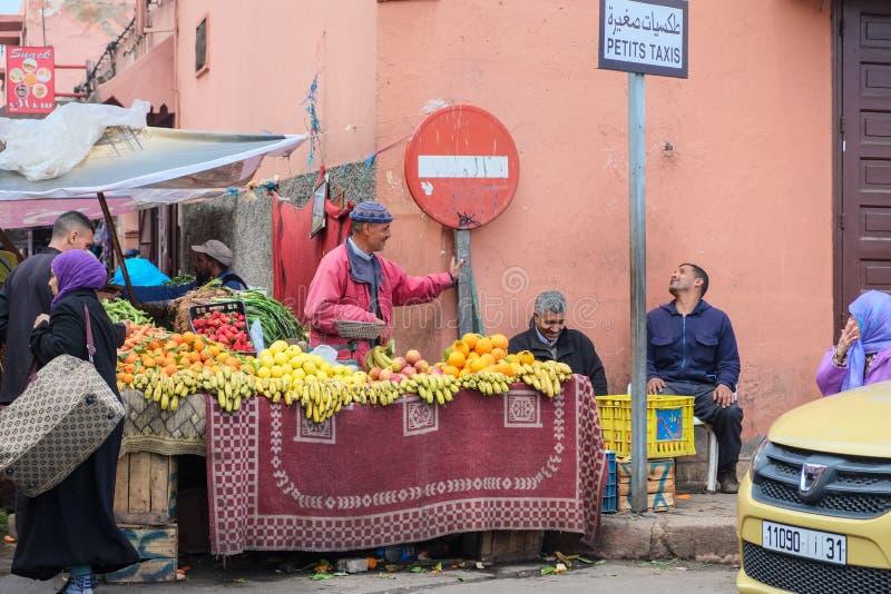 水果和蔬菜卖主与人谈话在新鲜市场上在没有词条标志附近 免版税库存照片
