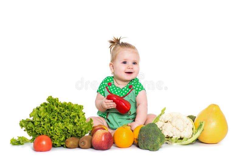 水果和蔬菜围拢的女婴开会,隔绝在白色 库存图片