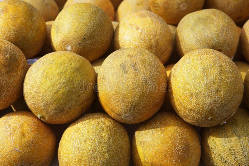 水果市场瓜行堆积了黄色 免版税库存照片