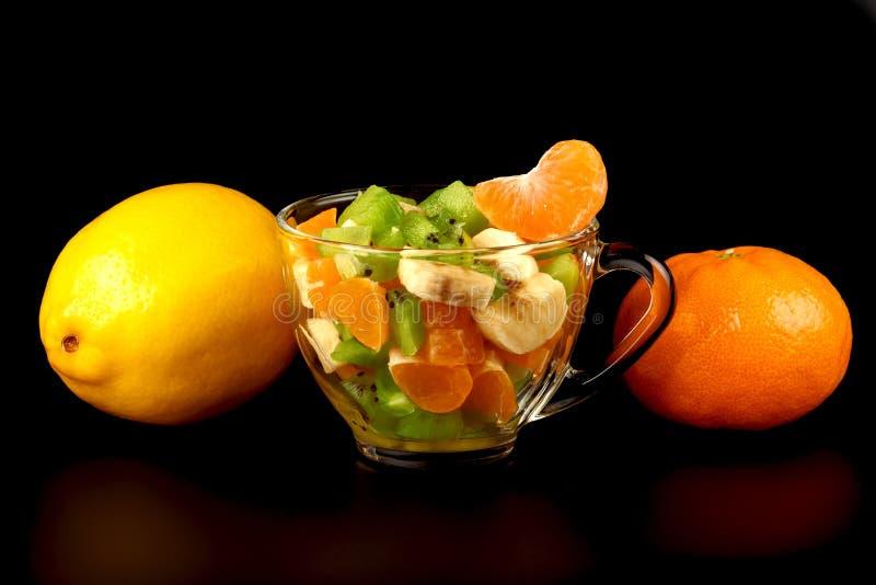 水果沙拉、蜜桔的柠檬、与饮料的段和玻璃 库存图片