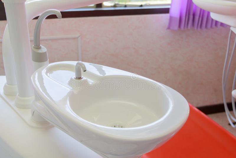 水槽医疗设备牙医关闭,陶瓷痰盂和水补白在诊所 免版税图库摄影