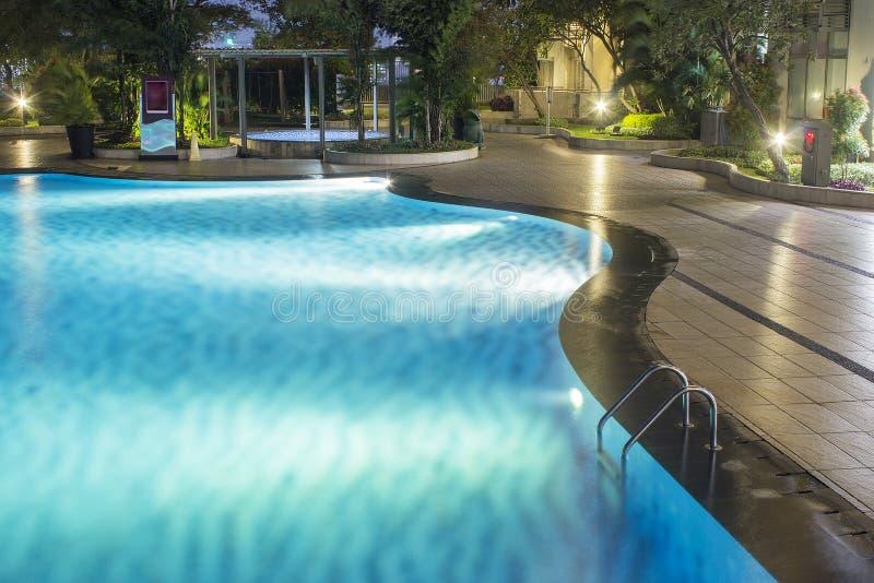 水池在与豪华的绿叶的家庭设计的夜和照明设备和环境美化里在后院 夜阴影和反射在t 免版税库存照片