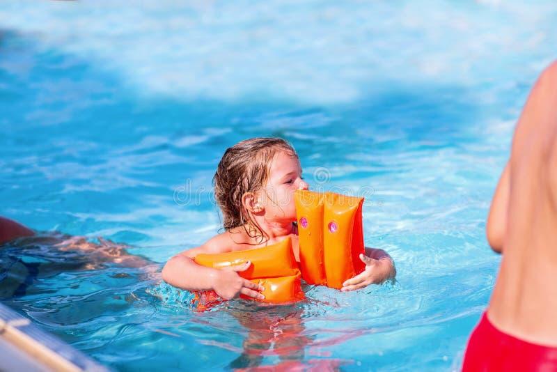 水池微笑的女孩获得乐趣在游泳场 免版税库存图片