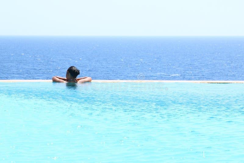 水池的年轻女人由海 库存照片