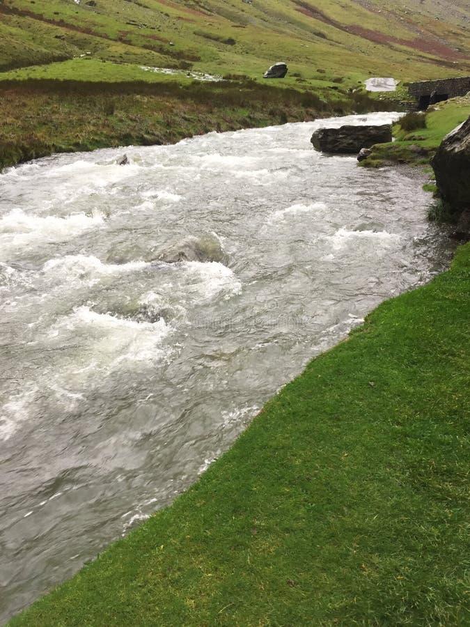 水洪流在涌出在小山下的山河 免版税图库摄影