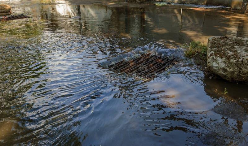 水流程在大雨期间和堵塞街道污水 水流程在风暴下水道的猛烈的飓风期间 污水 免版税库存图片