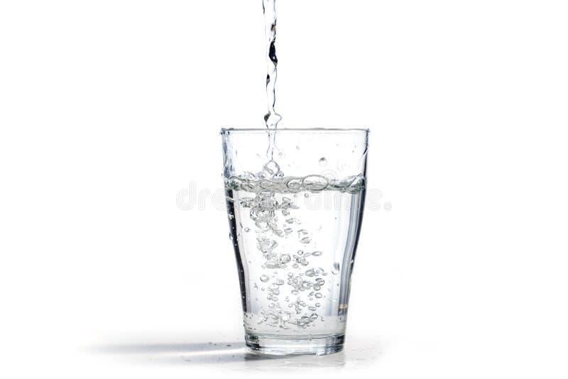 水涌入水杯,隔绝在一白色backg 库存图片