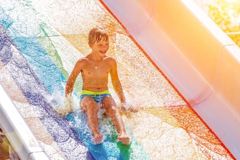 水滑道的一个愉快的男孩在游泳池获得乐趣在暑假时在一个美丽的水色公园 一个男孩 免版税图库摄影