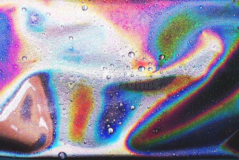 水滴在充满活力的全息照相的霓虹背景的 免版税库存照片