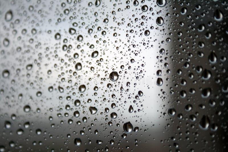 水滴在玻璃的反对被弄脏的黑暗的轻的梯度背景在一多雨阴天 r 库存图片