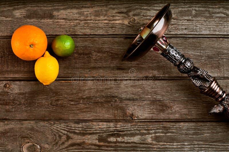 水烟筒的被取消的部分在木背景的用石灰果子 图库摄影