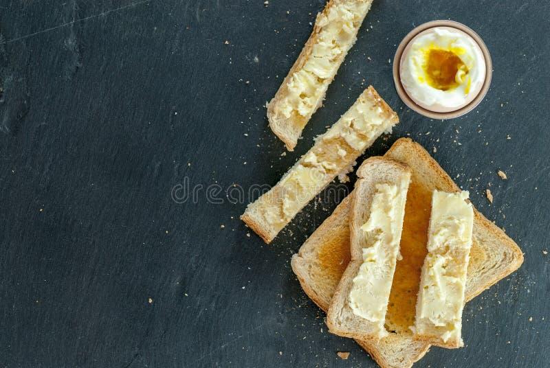 水煮蛋和多士在与黄油早餐概念的切片上添面包 免版税图库摄影